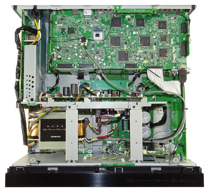 Der Blick ins Innere verrät die Familienherkunft des TX-RZ1100: Wie bei seinem großen Bruder TX-RZ3100 sitzen die Digital-Endstufen abgekapselt in einem Metallkäfig unterhalb der hinteren Platinen für die Analog-Sektion. Kühlkörper entfallen, vorne links sitzt der Transformator.